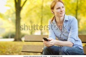 stock-photo-thoughtful-young-woman-sits-on-a-bench-in-a-park-and-listens-to-music-or-a-podcast-on-a-smartphone-230957515